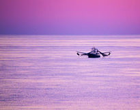 在紫罗兰色天空中的渔船在海湾 库存照片