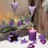 在紫罗兰色或紫色的圣诞节装饰与木头和一个蜡烛 库存图片