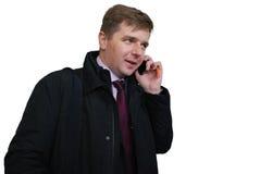 在紫罗兰色领带的愉快的典雅的商人由电话讲话 库存图片