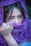 在紫罗兰色织品盖的亚洲美丽的夫人 图库摄影