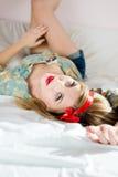 在年轻美丽的白肤金发的妇女牛仔裤的特写镜头短缺说谎在后面白色床上的花卉衬衣把您的脚放在墙壁上 库存照片