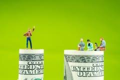 在100美元钞票边缘的微型小雕象讨论 免版税库存图片