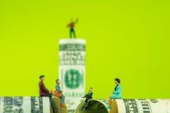在100美元钞票边缘的微型小雕象讨论 库存照片