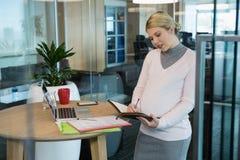 在组织者的怀孕的女实业家文字 免版税图库摄影