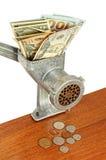 在绞肉机的美元在木桌上的钞票和硬币 免版税库存照片