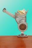 在绞肉机的美元钞票在天蓝色的背景 免版税库存图片