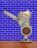 在绞肉机的美元钞票在蓝色砖墙背景 M 库存图片