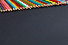 在黑背景关闭隔绝的颜色铅笔 库存照片