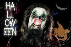 在黑背景前面的可怕小丑用南瓜和te 免版税图库摄影