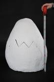 在黑背景的一个巨大的纸型鸡蛋与一卷测量的磁带 免版税图库摄影