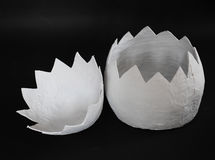在黑背景的一个巨大的纸型鸡蛋在两部分中被揭露 免版税库存照片