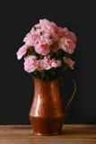 在黑背景的一个铜花瓶与桃红色微型康乃馨 库存照片