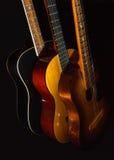 在黑背景的三把声学吉他 免版税库存照片