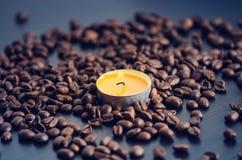 在黑背景的咖啡豆与蜡烛 未加工的咖啡豆和火从蜡烛 成颗粒状的产品 热的饮料关闭 免版税图库摄影