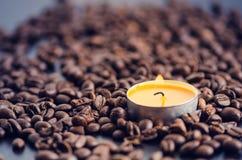 在黑背景的咖啡豆与蜡烛 未加工的咖啡豆和火从蜡烛 成颗粒状的产品 热的饮料关闭 免版税库存照片
