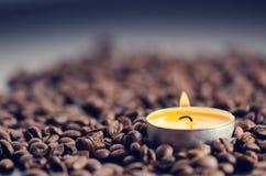 在黑背景的咖啡豆与蜡烛 未加工的咖啡豆和火从蜡烛 成颗粒状的产品 热的饮料关闭 库存照片