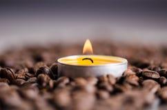 在黑背景的咖啡豆与蜡烛 未加工的咖啡豆和火从蜡烛 成颗粒状的产品 热的饮料关闭 库存图片