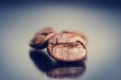 在黑背景的咖啡豆 原始豆的咖啡 成颗粒状的产品 热的饮料关闭 库存照片