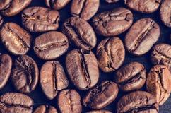 在黑背景的咖啡豆 原始豆的咖啡 成颗粒状的产品 热的饮料 关闭 免版税库存图片