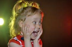 在黑背景的情感小女孩特写镜头与明亮 库存照片