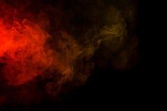 在黑背景的抽象红色和黄色烟水烟筒 免版税库存照片