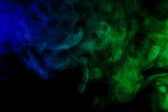 在黑背景的抽象蓝色和绿色烟水烟筒 库存图片