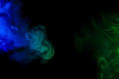 在黑背景的抽象蓝色和绿色烟水烟筒 免版税库存照片