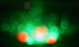在黑背景的抽象绿色,橙色bokeh 免版税库存照片