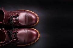 在黑背景的时兴的精神皮革褐色鞋子 人的高起动 顶视图 复制空间 免版税库存图片
