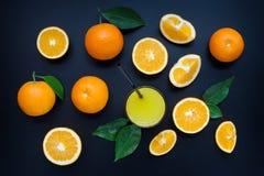 在黑背景的橙汁 库存照片