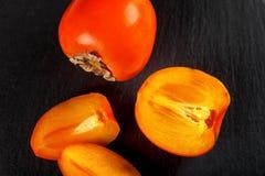 在黑背景的甜成熟柿子 免版税库存图片