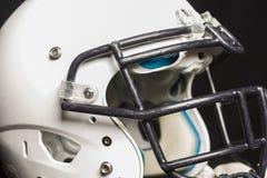 在黑背景的白色橄榄球盔 免版税图库摄影