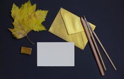 在黑背景的秋天叶子与卡片邀请和金黄 图库摄影