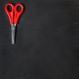 在黑背景的红色剪刀 免版税图库摄影