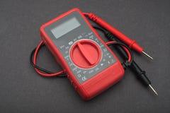 在黑背景的红色多用电表 免版税库存图片