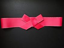 在黑背景的红色弓 免版税库存图片