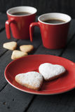 在黑背景的红色杯子和曲奇饼心脏 免版税库存图片