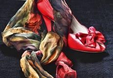在黑背景的红色高跟鞋和丝绸围巾 库存图片