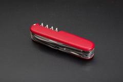 在黑背景的红色multitool刀子 免版税图库摄影