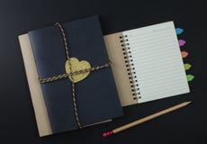 在黑背景的纸笔记本铅笔 免版税库存照片