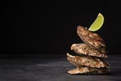 在黑背景的美丽的闭合的牡蛎 与水多的石灰的开胃海软体动物 昂贵的海洋成份 免版税库存图片