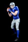 在黑背景的美国橄榄球运动员投掷的球 免版税库存照片
