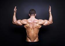 在黑背景的肌肉男性后面 免版税库存图片