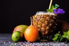 在黑背景的菠萝、芒果,柑橘,薄荷和新鲜薄荷 不同的异乎寻常的果子的构成 免版税图库摄影