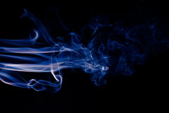 在黑背景的蓝色抽象烟设计 库存图片