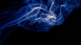 在黑背景的蓝色抽象烟设计 库存照片