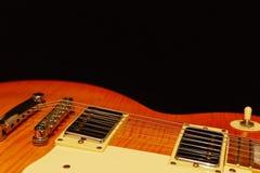 在黑背景的蜂蜜镶有钻石的旭日形首饰的电吉他特写镜头 浅深度的域 库存图片