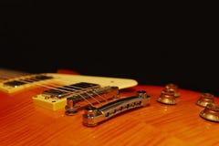 在黑背景的蜂蜜镶有钻石的旭日形首饰的电吉他特写镜头,与大量拷贝空间 选择聚焦 免版税图库摄影
