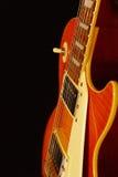 在黑背景的蜂蜜镶有钻石的旭日形首饰的电岩石吉他特写镜头 浅深度的域 免版税库存照片