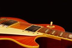 在黑背景的蜂蜜镶有钻石的旭日形首饰的电爵士乐吉他特写镜头 浅深度的域 免版税库存照片